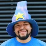 Kevin Kaland wizonesolutions smiling wearing a wizard hat with a yellow star on it and blue T shirt