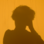 The shadow of a head on a yellow wall.